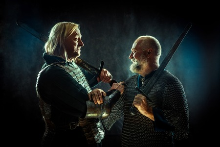 Medieval knights are crossing their hands in the brotherhood of War. Dark background. Stock Photo