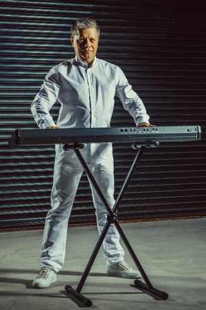 Artist playing on the keyboard synthesizer piano keys. Male musician plays a musical instrument.