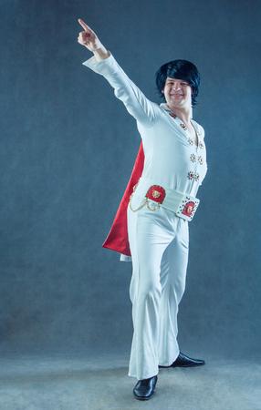 Smiling rockstar in white vintage costume in studio.
