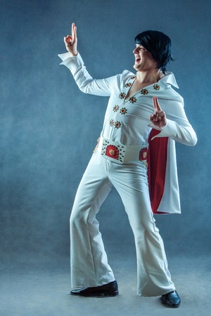 Smiling rockstar in white vintage costume in studio.