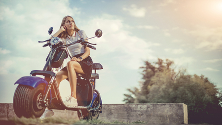 Young Woman Riding Electro Scooter On Country Road Stock Photo