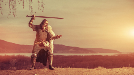 Long haired knight with the two-handed sword. Medieval rural background. Stockfoto
