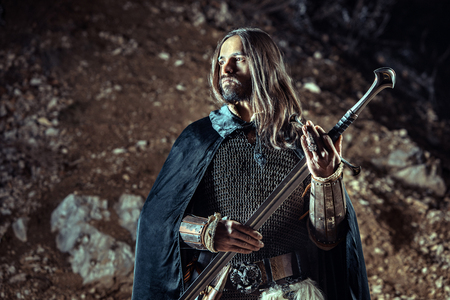 Long haired knight with the two-handed sword. Rocks on the background. Stock Photo