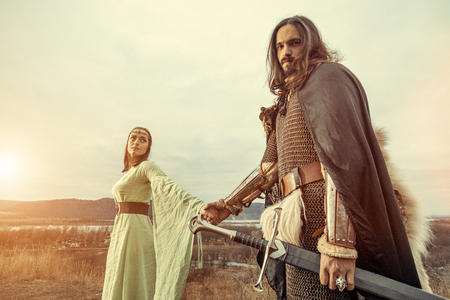 Mittelalterlicher Ritter mit Dame auf dem Sonnenunterganghintergrund Standard-Bild