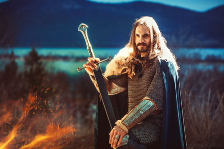 Long haired knight with the two-handed sword. Summer night on the background.