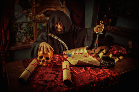 Necromancy sorcerer casting black magic spell using blind skull Stock Photo
