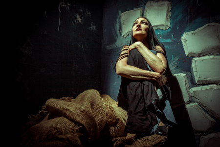 A woman sitting alone in the dark prison cell.
