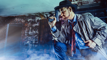 Detective with the gun wearing a fedora hat and a trench coat, dark background. Archivio Fotografico - 119184423