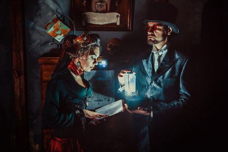 Woman is reading a book in a dark room. Her husband is holding a lamp. Banque d'images