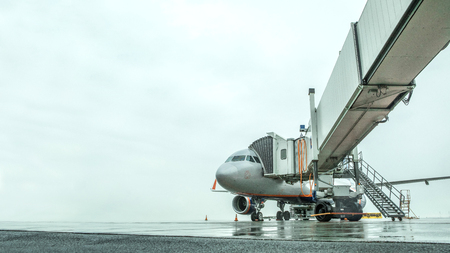 White unrecognizable airplane at the airport takes passengers through a telescopic ladder