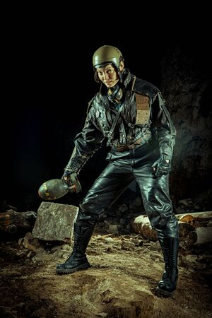 Soldier woman with the bomb on post apocalyptic background. Stock fotó