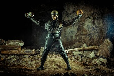 Soldier woman with the bomb in one hand and skull in another on the ruined background.