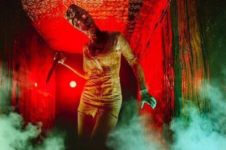Scary undead zombie in the dark corridor. Halloween theme. 免版税图像