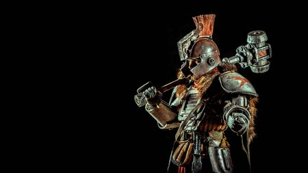 Powerful knight in the armor with the hammer. Dark background.