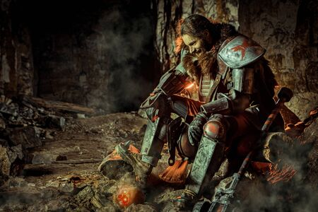 Powerful knight in the armor with the hammer is sitting on the stone. Dungeon on the background. Imagens