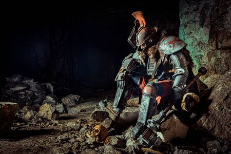 Powerful knight in the armor with the hammer is sitting on the stone. Dungeon on the background. Stock Photo