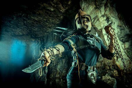 Femme post-apocalyptique au casque rouillé avec une chaîne et un couteau dans les mains sur le fond du donjon. Temps post-apocalypse nucléaire. La vie après la fin du monde