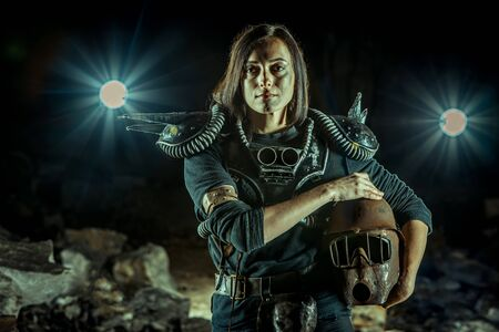 Post-apocalyptic woman with the rusty helmet in hands on the dungeon background. Nuclear post-apocalypse time. Life after doomsday