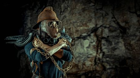 Post-apocalyptic woman in the rusty helmet with a chain in hands on the dungeon background. Nuclear post-apocalypse time. Life after doomsday Reklamní fotografie