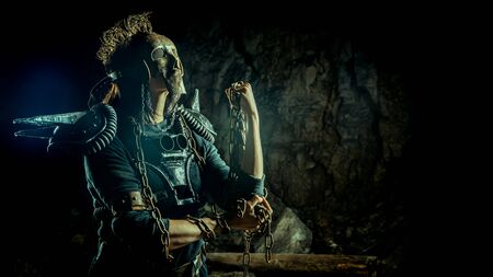 Post-apocalyptic woman in the rusty skull mask on the dungeon background. Nuclear post-apocalypse time. Life after doomsday Reklamní fotografie