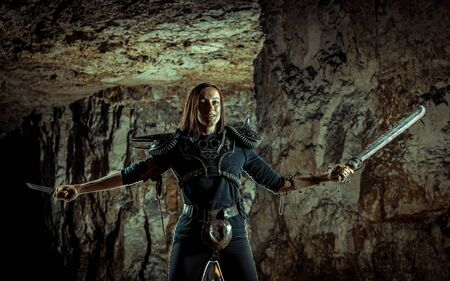 Post-apocalyptic woman with the chain and sword in hands on the dungeon background. Nuclear post-apocalypse time. Life after doomsday