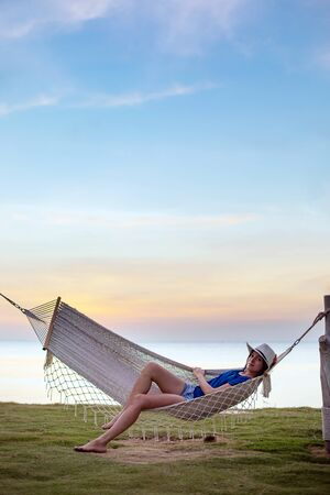 Young beautiful woman in hammock on the Phu Quoc island, Vietnam.