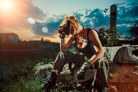 Sexy woman soldier with pistol is having a rest. Sunset on the background.