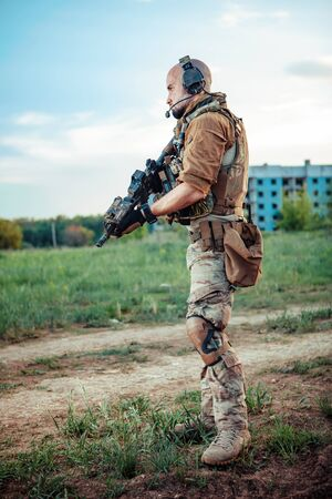 American soldier with the M4 rifle on the ruined town background. Stok Fotoğraf