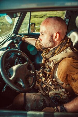 Bald soldier in uniform is driving military vehicle. Stok Fotoğraf