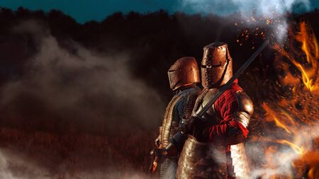 Two Medieval knights armed with axe and sword. Stock Photo