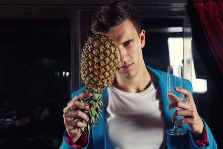 Man holding glass of champagne in one hand and pineapple in the other.