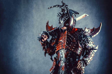 Powerful knight in the armor with the sword. Dark background. Archivio Fotografico