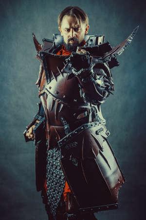 Powerful knight in the armor. Dark background. Archivio Fotografico