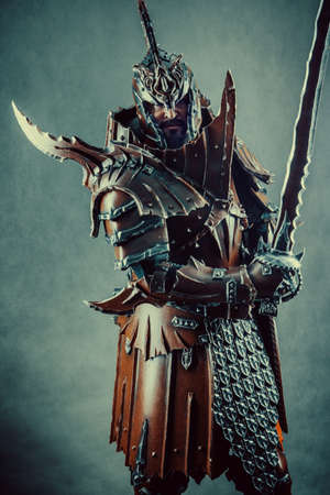 Powerful knight in the armor with the sword. Dark background. Stock Photo