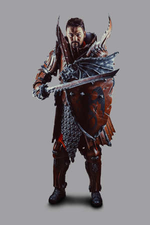 Powerful knight in the armor with the sword and shield. Isolated over grey background.