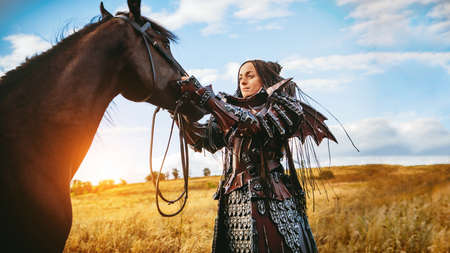 Girl in medieval knight's armor with a horse against the sunset fields background Archivio Fotografico