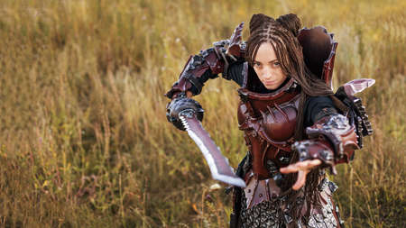 Girl in medieval knight's armor with a big sword against the sunset fields background Archivio Fotografico