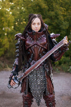 Girl in medieval knight's armor with a big sword against the green trees background Archivio Fotografico