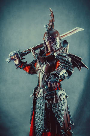 Portrait of a medieval female knight in armor with sword over grey background.