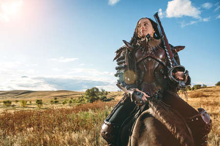 Knight woman in armor on the horse against the sunset fields background