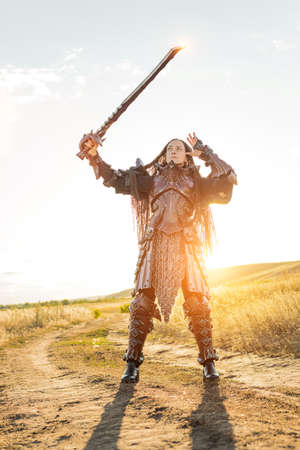 Knight woman in armor with a horse against the sunset fields background
