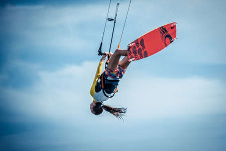 kiter: A young woman kite-surfer rides in greenish-blue sea under clear skies Stock Photo