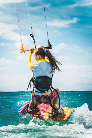 A young woman kite-surfer rides in greenish-blue sea under clear skies 스톡 콘텐츠