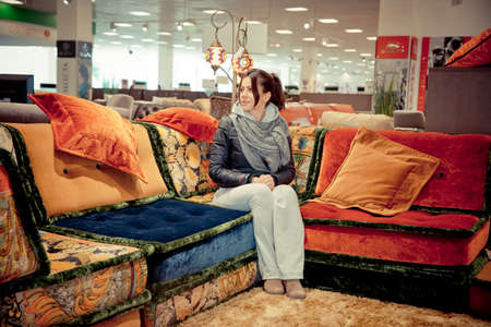 furniture store: Woman sitting on new red sofa in furniture store, stroking armrest, holding shopping bags, smiling