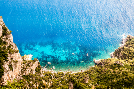 Top down view on a blue clean turquoise lagoon with a boat. Clear view from the above on a tranquil blue lagoon. Lonely motor boat is floating on a blue lagoon waters. High cliffs surround lagoon from the ocean.