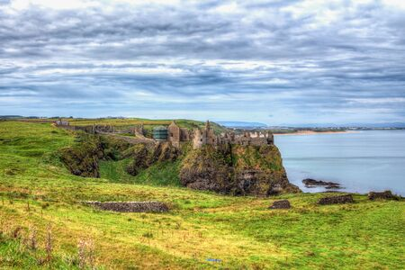 Ancient castle built on a rock surrounded by sea. Tone mapped high definition range photo of an old castle risen on a hight cliff rock surrounded by deep water with a beautiful cloudy skyline and emerald glen.