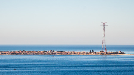 Narrow seashore with a city and tall antenna at the end. Narrow peninsula city surrounded with tranquil sea waters. At the end of the peninsula there is an antenna. Clear sky without a single cloud that lasts to the horizon.