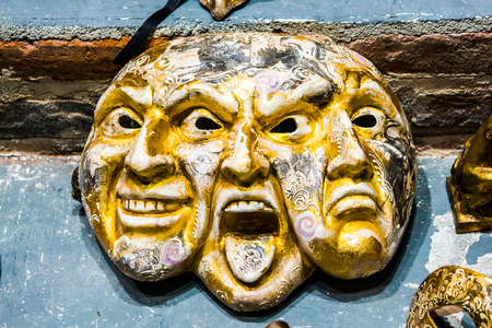 Venice mask of triple face happy, angry and sad. Original unique golden color Venice mask of three faces happy, angry and sad merged into one.