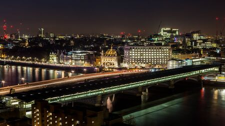 Blackfriars Bridge over the Thames at night. Panoramic view of the river and deserted streets of London far into the night near Blackfriars Bridge Stock Photo