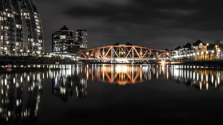 Industrial steel bridge over a still river at night. Long reflections a the bridge and nearby houses are seen on the river surface. Illuminated objects of a different color contrasting with a dark sky. Stock Photo